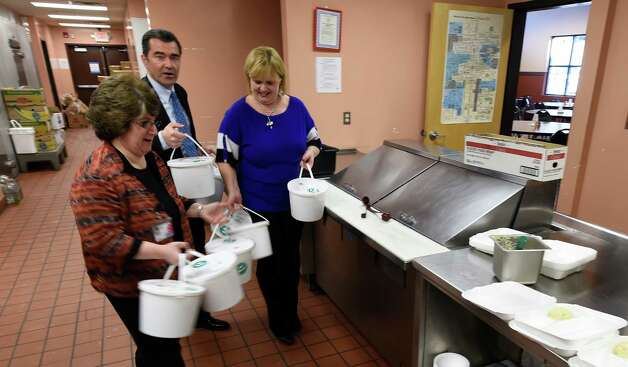 Mona Golub, vice president for public relations and customer service, the Golub Corp., left, Mike Saccociao, executive director, Schenectady City Mission, center, and Christina Rajotte of Equinox carry tubs of turkey soup into the City Mission of Schenectady Tuesday morning, Dec. 2, 2014, in Schenectady, N.Y.  The soup was part of Project Soup initiated by Price Chopper and Equinox to produce more than 150 gallons of soup which will be distributed to kitchens and food pantries throughout the Capital District.   (Skip Dickstein/Times Union) Photo: SKIP DICKSTEIN / 00029700A