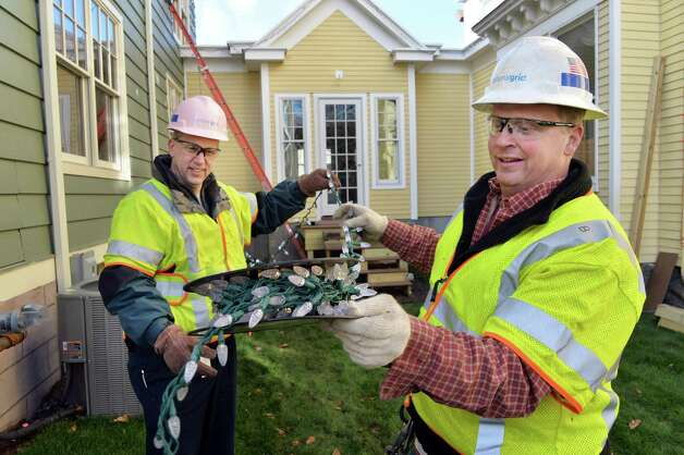 National Grid fleet manager Larry Reisigl, left, and hot stick line foreman Steve Blydenburgh, right, help to decorate the Ronald McDonald House with energy efficient holiday lights Tuesday Dec. 2, 2014, in Albany, N.Y. National Grid used the decorations to demonstrate the use of energy efficiency solutions such as LED lighting and advanced power strips, which can allow homeowners and businesses to spend less money on electricity. (John Carl D'Annibale / Times Union) Photo: John Carl D'Annibale / 00029704A