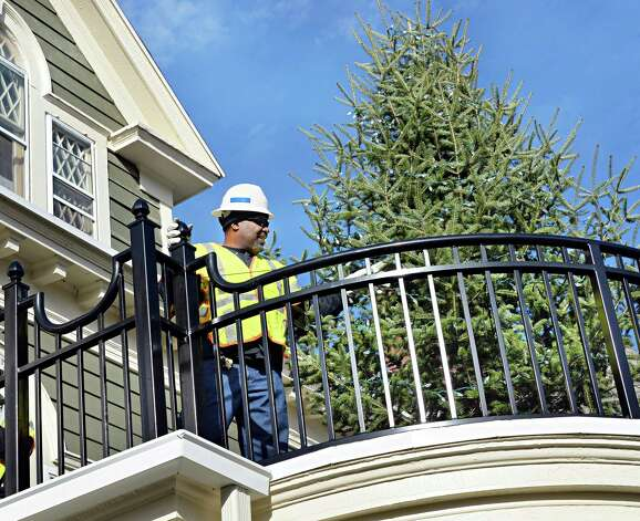 National Grid volunteer Clarence Timmons of Albany straightens a Christmas tree after his co-workers used a bucket truck to place it on a second floor balcony at the Ronald McDonald House Tuesday Dec. 2, 2014, in Albany, N.Y. National Grid used the decorations to demonstrate the use of energy efficiency solutions such as LED lighting and advanced power strips, which can allow homeowners and businesses to spend less money on electricity. (John Carl D'Annibale / Times Union) Photo: John Carl D'Annibale / 00029704A