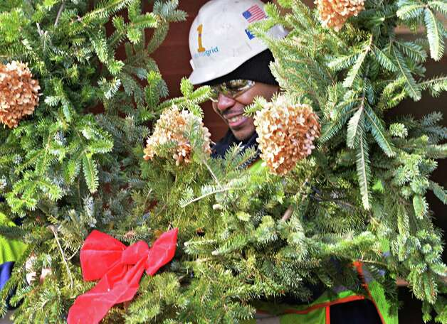 National Grid volunteer Floyd Harris hangs a holiday wreath as he and dozens of co-workers decorate the Ronald McDonald House for the Holidays Tuesday, Dec. 2, 2014, in Albany, N.Y.  National Grid used the decorations to demonstrate the use of energy efficiency solutions such as LED lighting and advanced power strips, which can allow homeowners and businesses to spend less money on electricity. (John Carl D'Annibale / Times Union) Photo: John Carl D'Annibale / 00029704A