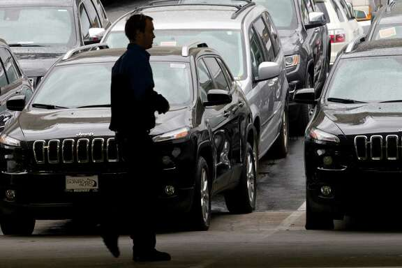 A worker on a Chrysler car lot passes lines of mostly Jeep SUVs Tuesday, Dec. 2, 2014, in San Diego. Black Friday promotions, coupled with falling gas prices, low-interest loans and hot new vehicles, drove U.S. auto sales higher in November, kicking off what's expected to be a strong holiday season. Chrysler, which sells Jeep cars, posted its best November in 13 years. (AP Photo/Gregory Bull)