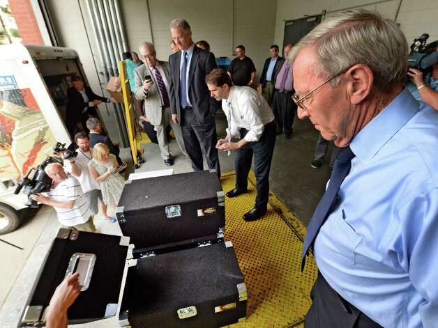 Mayor Dan Dwyer, right, watches as bids for the Rensselaer casino development are delivered at the New York State Gaming building Monday morning June 30, 2014 in Schenectady, N.Y.    John Signor, center, of the Capital OTB also was present for the delivery.  The deadline for bids to hold a license for one of seven full service casinos in New York State ended Monday at 4 p.m.   (Skip Dickstein / Times Union) Photo: SKIP DICKSTEIN / 00027558A
