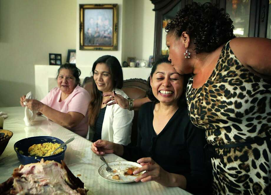 """Elizabeth Resendiz, right, a Honduran who immigrated to the U.S. back in the 80's, hugs and kisses Lesly Cabrera, also from Honduras, who immigrated to San Antonio with her 16 year old son Edwuard Salgado Cabrera this year in May. Resendiz hosted a Thanksgiving dinner for 20 family members and friends which was the first Thanksgiving for Cabrera.  With them at the table are Maira Paredes, left, also from Honduras, and Cristina Montes a friend from church.  Cabrera tasted new foods during the meal including a roasted whole turkey, cranberry sauce and pumpkin pie. She said, I give God thanks for the opportunity  to be here safe with family, and such a big feast"""".  She has an immigration court date in January before a judge to see if she gets asylum.  Thursday, Nov. 27, 2014. Photo: BOB OWEN, San Antonio Express-News / © 2014 San Antonio Express-News"""