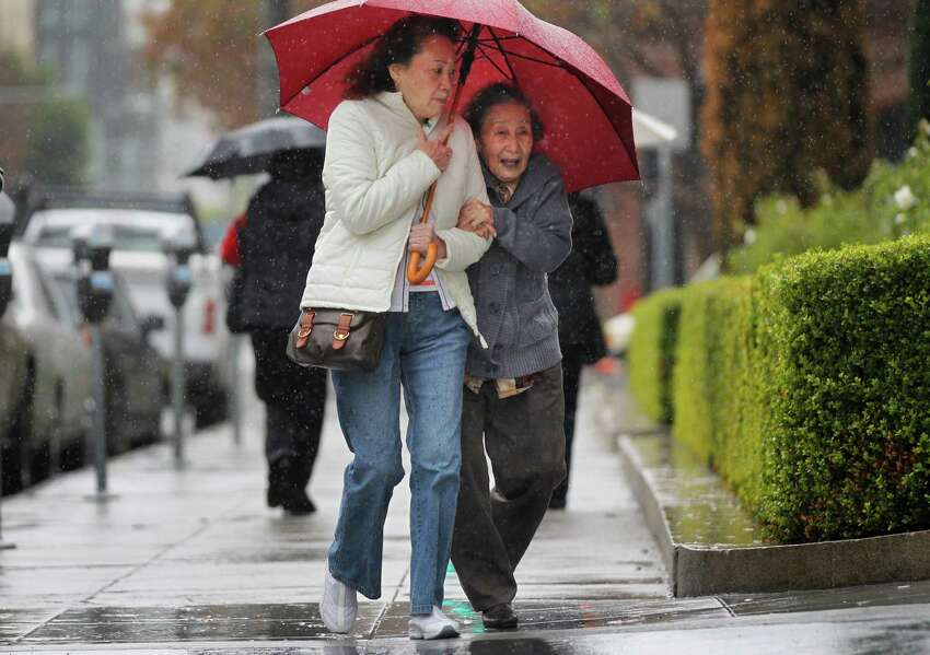Cindy Wong (left) shelters her mother, Yim, 82, from the rain under an umbrella as they walk to a restaurant in San Francisco on Tuesday.