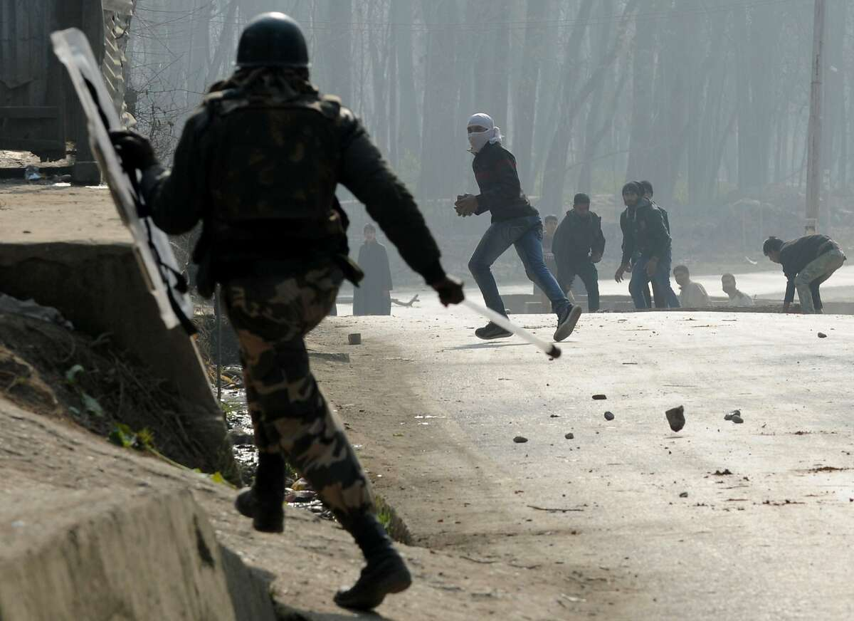 TOPSHOTS Kashmiri protestors throw stones and shout pro-freedom slogans during a clash with Indian police near a polling station in Koimoh Kulgam, south of Srinagar, on December 2, 2014. Indian Kashmir headed to the 2nd phase of polls under tight security with Prime Minister Narendra Modi's Hindu nationalist party eyeing power for the first time in the tense and disputed Muslim-majority state. AFP PHOTO/Rouf BHATROUF BHAT/AFP/Getty Images