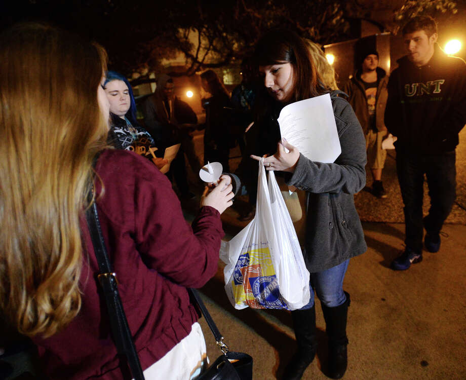 Shelby Murphy passes out candles for Tuesday's vigil. The Lamar Democratic Socialists hosted a candlelight vigil to protest the Ferguson grand jury decision on Tuesday evening. About 20 students attended. Photo taken Tuesday 12/2/14 Jake Daniels/The Enterprise Photo: Jake Daniels / ©2014 The Beaumont Enterprise/Jake Daniels