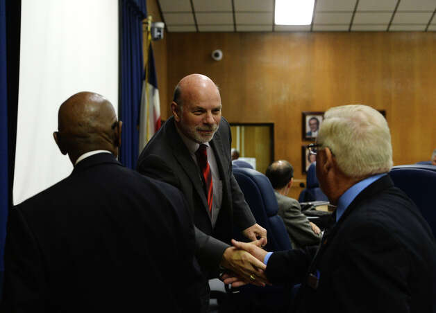Superintendent Vern Butler, center, reaches out to shake hands with James Davis, left, and Bill Newman, right, of Ray and Associates after their presentation Tuesday. The Beaumont ISD board of managers heard presentations from three superintendent search firms Tuesday afternoon. Photo taken Tuesday 12/2/14 Jake Daniels/The Enterprise Photo: Jake Daniels / ©2014 The Beaumont Enterprise/Jake Daniels