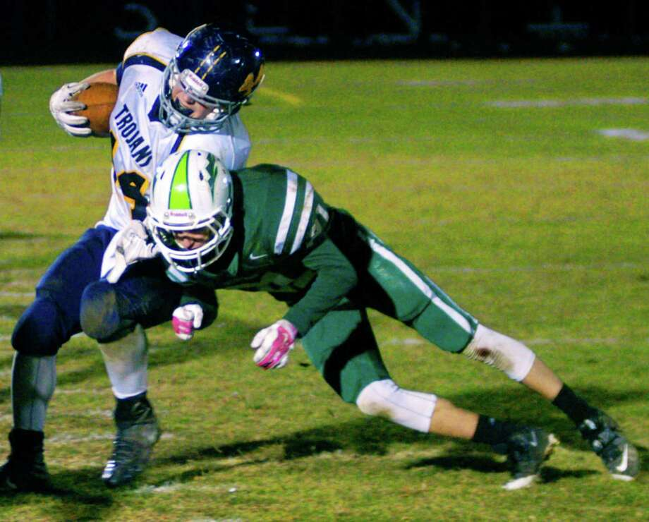 The Green Wave's Kyler Cyr uses every bit of leverage he can muster to shove a tough Trojan ballcarrier out of bounds during New Milford High School football's 34-20 defeat to Weston, Nov. 14, 2014 at NMHS.during New Milford High School football's 34-20 defeat to Weston, Nov. 14, 2014 at NMHS. Photo: Norm Cummings / The News-Times