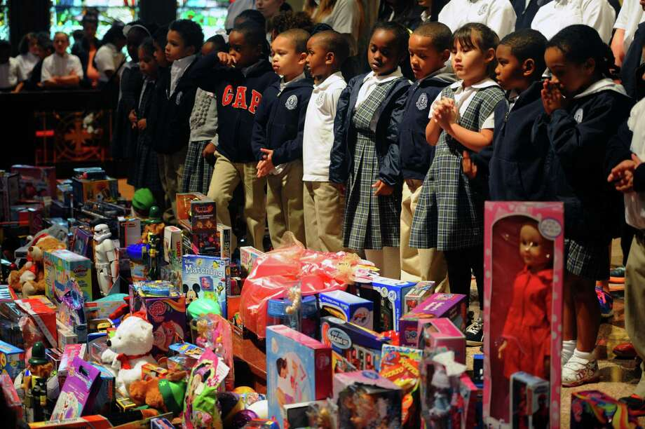 St. Anthony students stand Wednesday at the St. Joseph alter with around 400 toys to be donated to the E.J. Empty Stocking Fund.