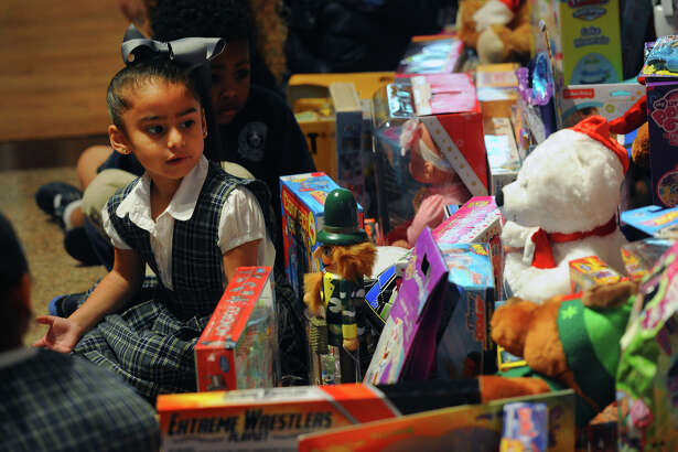 Averi Hernandez, 3, looks at the toys collected by St. Anthony students on Wednesday. The toys will be donated to the E.J. Empty Stocking Fund. Photo taken Wednesday, December 04, 2014 Guiseppe Barranco/The Enterprise
