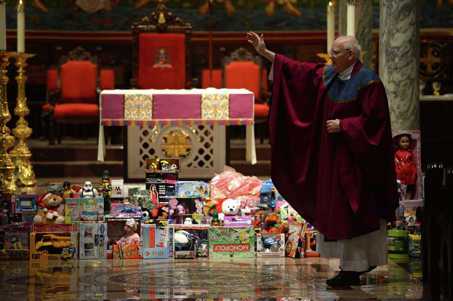 The Rev. Jerry McGrath gives a sermon during a special mass for St. Anthony students the at St. Anthony Basilica on Wednesday. Around 400 toys were collected during the service for the E.J. Empty Stocking Fund.