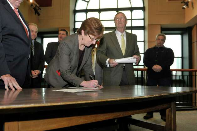 Albany Mayor Kathy Sheehan signs a letter showing support for the casino site in Rensselaer as Rensselaer Mayor Dan Dwyer, right, looks on at a press event to show support for the Rensselaer casino site on Wednesday, Dec. 3,  2014, in Rensselaer, N.Y.    (Paul Buckowski / Times Union) Photo: Paul Buckowski / 00029722A