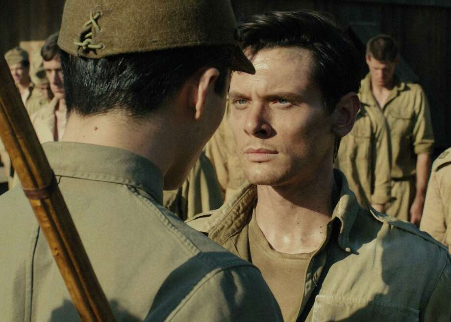 """The Bird (MIYAVI) torments Louis Zamperini (JACK O'CONNELL) in """"Unbroken,"""" directed by Angelina Jolie. Zamperini was an Olympic hero who survived a crash during his World War II service as a bombardier, only to end up in a Japanese prison camp for years. Movie opens Dec. 25. Photo: Universal Pictures / ONLINE_YES"""