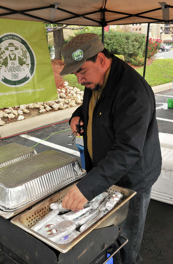 Adrian Magnifico tends to his tamales at his Gardeners Feast stall at the Quarry's Farmer's Market in 2011. Photo: ROBIN JERSTAD, FREELANCER / SPECIAL TO THE EXPRESS-NEWS / SAN ANTONIO EXPRESS-NEWS