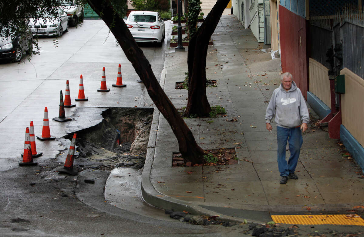 Ralph Geissler of San Francisco walks by a sinkhole that formed in front of his home on Danvers Street on Wednesday, December 3, 2014 in San Francisco, Calif.