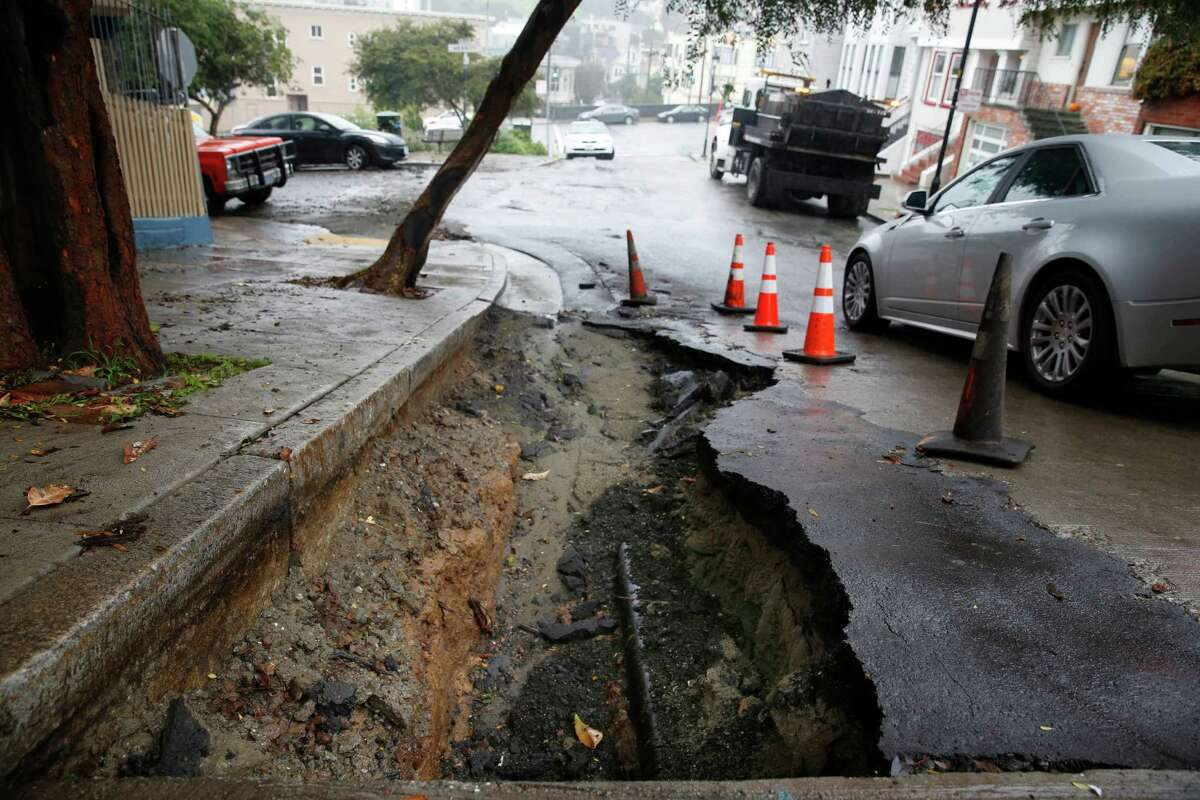 A car maneuvers past a sinkhole on Danvers Street on Wednesday, December 3, 2014 in San Francisco, Calif.
