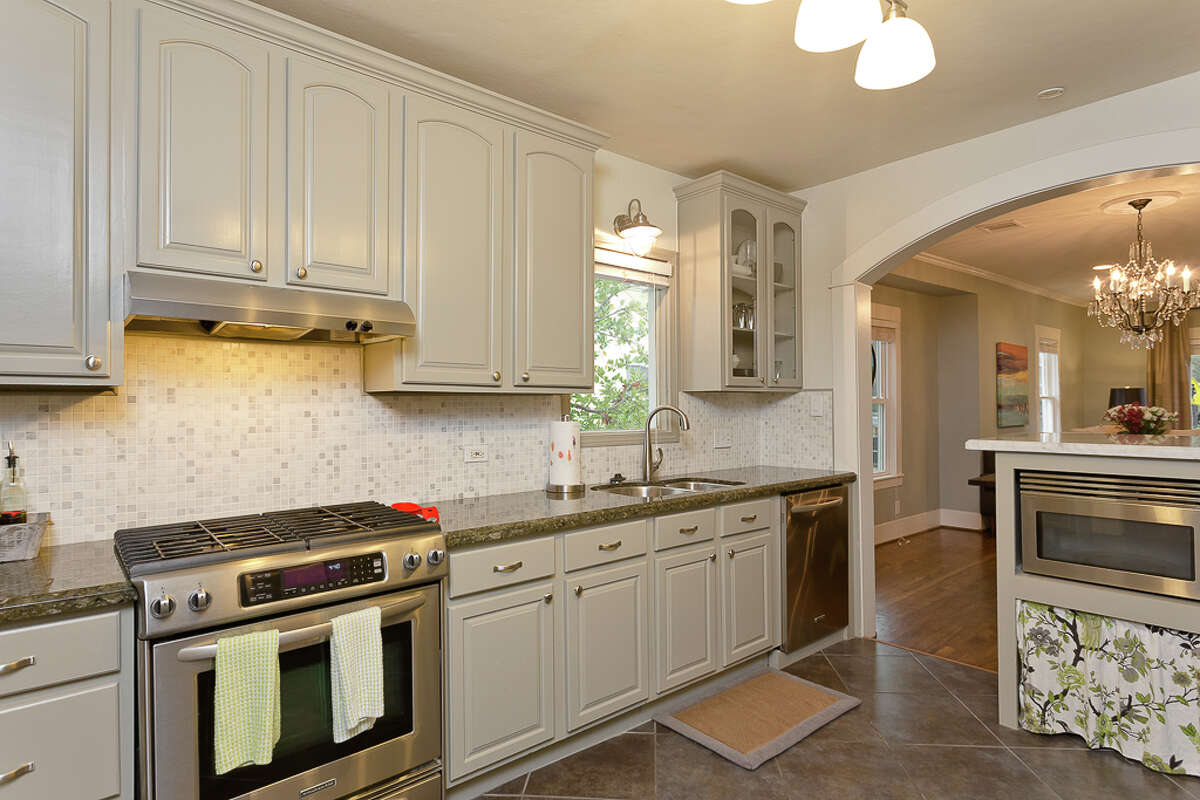 Soon after they moved in, Stephanie and Thomas Miles remodeled the kitchen. They took out part of one wall, replacing it with an arch that leads into the living room, and brightened wood cabinets with a light gray paint. The tile backsplash is Carrara marble.