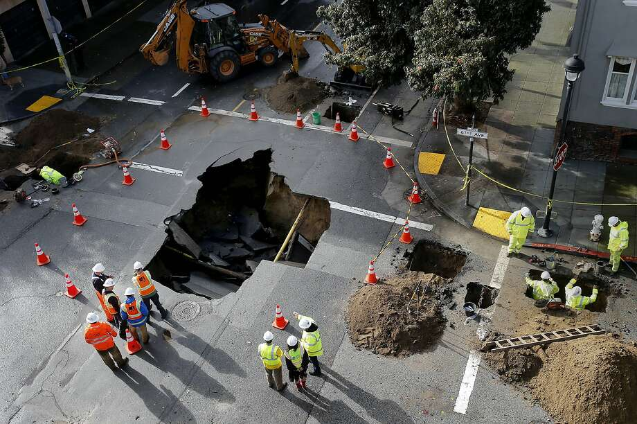 DPW crews worked to stop a sinkhole at 6th Avenue and Lake Streets in San Francisco, Calif. from getting worse. Another potent storm caused flooding and sinkholes and made the Marin county morning commute one of the worst ever Wednesday December 3, 2014. Photo: Brant Ward, The Chronicle