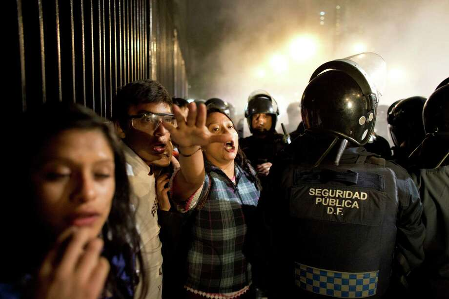 People react as they are cornered by riot police trying to contain remaining protestors, after anarchists smashed up banks and stores following a largely peaceful demonstration in Mexico City, Monday. Protesters marched in several cities in Mexico on Monday to mark the second anniversary of President Enrique Pena Nieto's administration and demand the government find 43 students who disappeared at the hands of police. Photo: Rebecca Blackwell / Rebecca Blackwell / Associated Press / AP