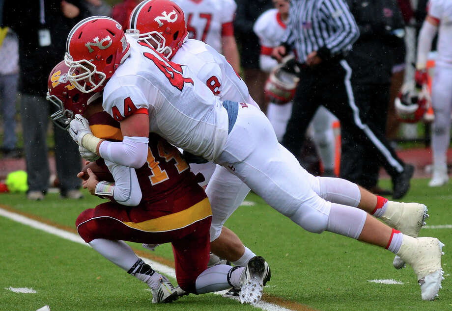 St. Joseph QB Cory Babineau gets sacked by New Canaan's Zachary Allen and David Strupp, in back, during football action in Trumbull, Conn. on Saturday, November 1, 2014. Photo: Christian Abraham / Connecticut Post