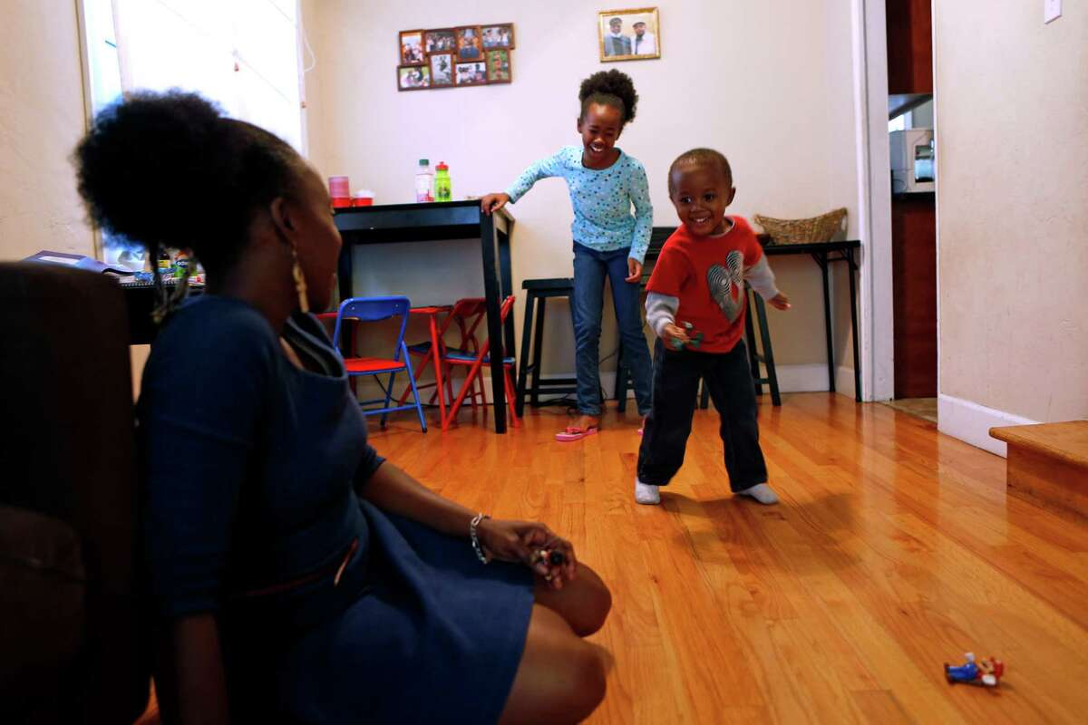 Kehinde Kujichagulia-Setu watches her son, Cameron, 3, dance as daughter, Xion, 10, laughs at the performance at their home in Oakland, Calif., on Wednesday, November 26, 2014.