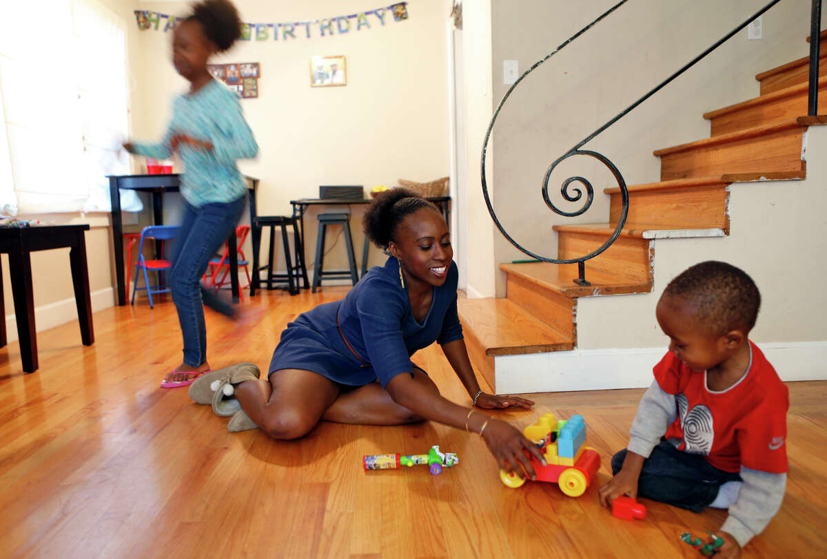 Kehinde Kujichagulia-Seitu plays with her son, Cameron, 3, as her daughter, Xion, 10, runs past at their Oakland home.