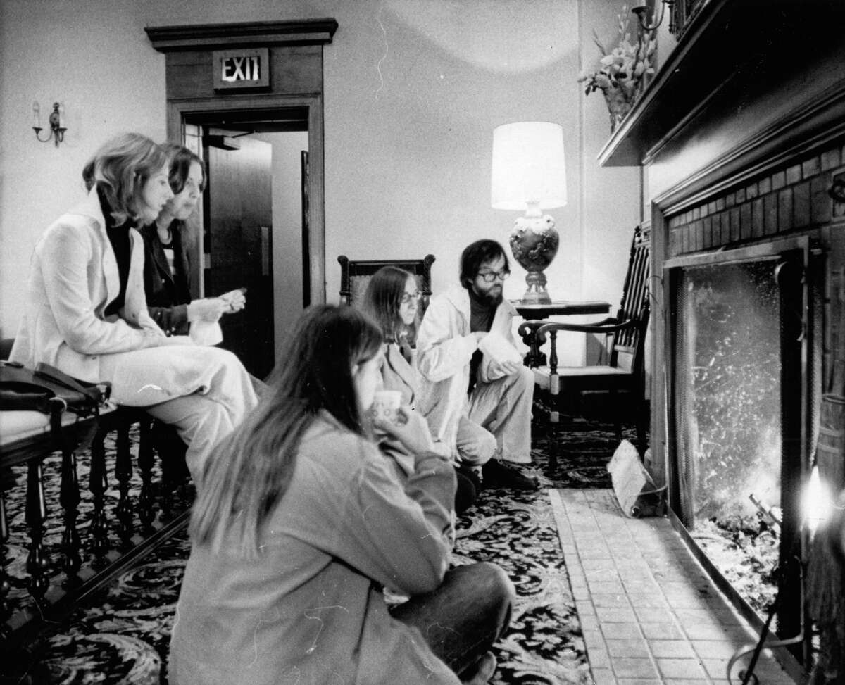 This will soon be a thing of the past: Sitting in front of the fireplace at the Harvard Exit theater. Movie goers also used to eat free snacks in the 1920s lobby, read newspapers and do jigsaw puzzles while waiting for their movie to start. Photo: 1972, P-I file.