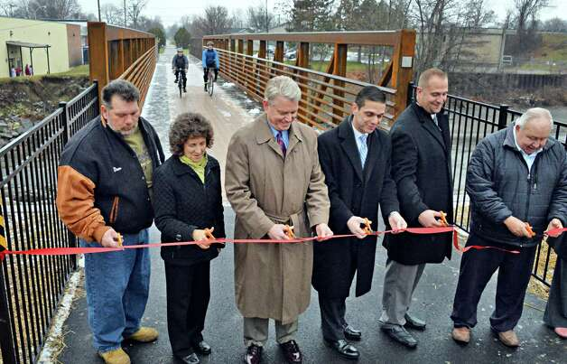 Brian Stratton, center, Director, New York State Canal Corp., joins state and local officials in a ribbon-cutting ceremony to mark the reopening of the newly reconstructed Erie Canalway Bridge over the Otsquago Creek Wednesday Dec. 3, 2014, in Fort Plain, NY.  (John Carl D'Annibale / Times Union) Photo: John Carl D'Annibale / 00029707A