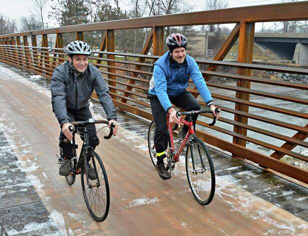 Greg Francese, left, and Jamie Meerdink of Parks and Trails New York ride their bikes over the newly reconstructed Erie Canalway Bridge over the Otsquago Creek Wednesday Dec. 3, 2014, in Fort Plain, NY.  (John Carl D'Annibale / Times Union) Photo: John Carl D'Annibale / 00029707A