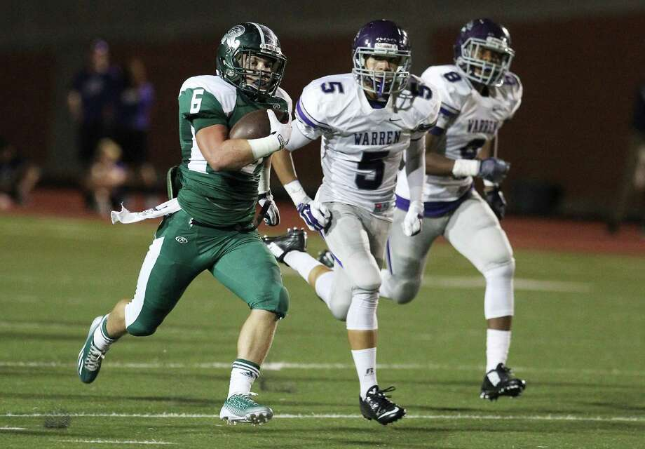 Reagan's Skyler Wetzel runs away from Warren's Jordan Sutherlin (5) and Keeshawn Payne during a game at Heroes Stadium on Sept. 12. Photo: Kin Man Hui, Staff / San Antonio Express-News / ©2014 San Antonio Express-News