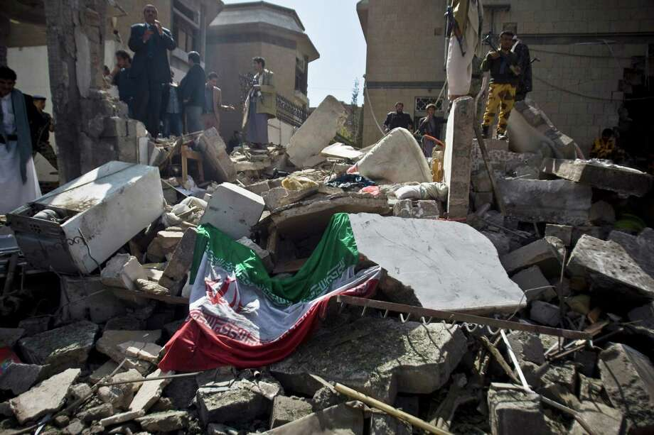An Iranian flag lies on the ground as people and police troopers gather at the damaged residence of the Iranian ambassador after a car bomb attack in Sanaa, Yemen, on Wednesday. Iran has been supporting Shiite Houthi rebels as part of its more open strategy of using its military power in the region. Photo: Hani Mohammed, STR / AP