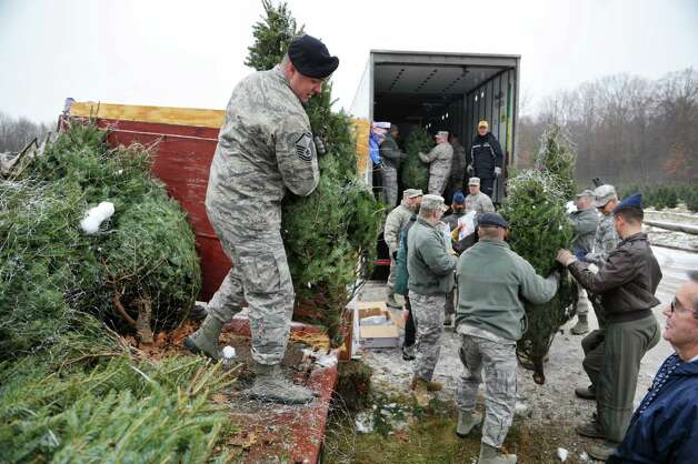 Master Sergeant Kyle Defeo, left, with the 109th Air National Guard helps load trees with other members of his unit and Army National Guard members a the Ellms Family Farm on Wednesday, Dec. 3,  2014, in Charlton, N.Y.  This is the tenth year of the Trees for Troops program in the Capital Region.  Some 16 farms donated trees for this years program which provides trees to military families at bases and overseas.  The program is run by the Christmas Spirit Foundation.    (Paul Buckowski / Times Union) Photo: Paul Buckowski / 00029635A