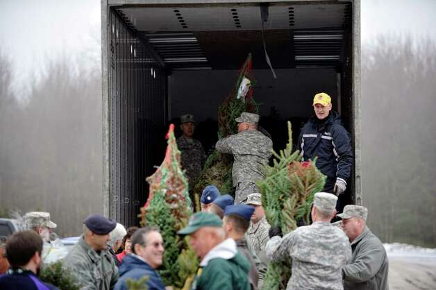 Soldiers with the Army National Guard and with the 109th Air National Guard help out at the Ellms Family Farm as they load trees on to a truck as part of the Trees for Troops program on Wednesday, Dec. 3,  2014, in Charlton, N.Y.  This is the tenth year of the Trees for Troops program in the Capital Region.  Some 16 farms donated trees for this years program which provides trees to military families at bases and overseas.  The program is run by the Christmas Spirit Foundation.    (Paul Buckowski / Times Union) Photo: Paul Buckowski / 00029635A