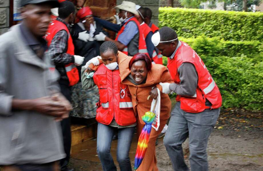A woman is assisted by Red Cross workers Tuesday as she is overcome by emotion after seeing the body of a relative who was killed in Tuesday's attack. Photo: Khalil Senosi, STF / AP