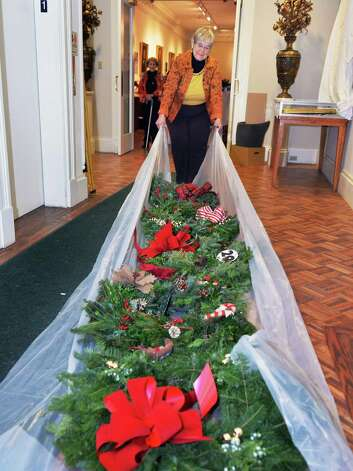 Mary Ellen Sullivan of Wynantskill moves holiday wreaths to be auctioned by the Van Rensselaer Garden Club during their annual Greens Show at the Rensselaer County Historical Society Tuesday, Dec. 2, 2014, in Troy, N.Y.  (John Carl D'Annibale / Times Union) Photo: John Carl D'Annibale / 00029691A