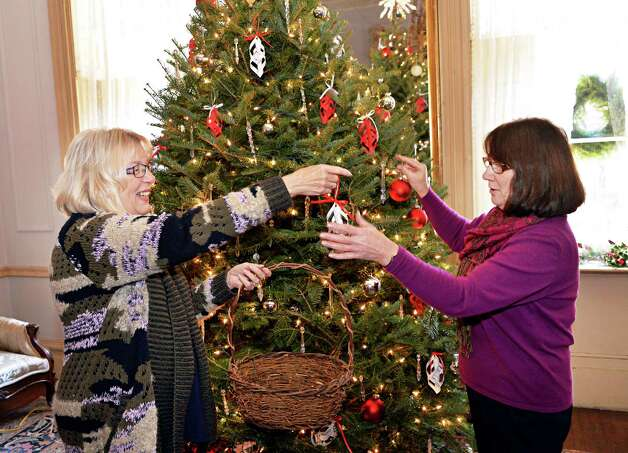 Van Rensselaer Garden Club chairwoman Maria Russo, left, and club member Joan Kruegler trim a Christmas tree in the Hart-Cluett House as they prepare for their annual Greens Show at the Rensselaer County Historical Society Tuesday, Dec. 2, 2014, in Troy, N.Y.  (John Carl D'Annibale / Times Union) Photo: John Carl D'Annibale / 00029691A