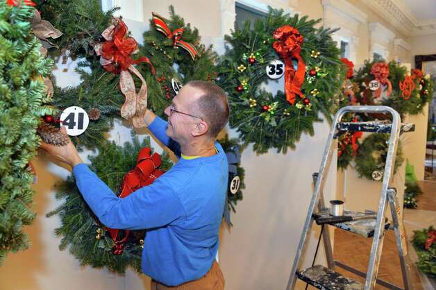 Kevin Kowski of Troy hangs holiday wreaths to be auctioned by the Van Rensselaer Garden Club during their annual Greens Show at the Rensselaer County Historical Society Tuesday, Dec. 2, 2014, in Troy, N.Y.  (John Carl D'Annibale / Times Union) Photo: John Carl D'Annibale / 00029691A