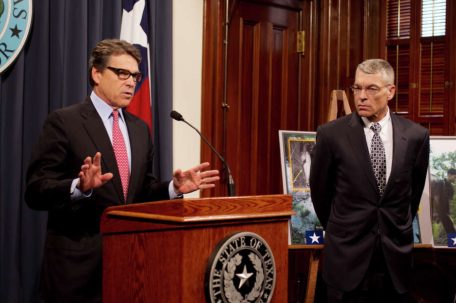 Texas Gov. Rick Perry, left, is joined by Texas Department of Public Safety Director Steve McGraw, during a news conference on Wednesday, Dec. 3, 2014 at the Capitol in Austin.  The Obama administration's executive action on immigration could trigger a new flood of people pouring across the Texas-Mexico border,  Perry said Wednesday. (AP Photo/Austin American-Statesman, Deborah Cannon) Photo: Deborah Cannon, MBO / Austin American-Statesman