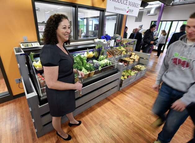 Amy Klein greets visitors at the grand opening of the Capital District Community Gardens' Urban Grow Center, which also received a brand name change to Capital Roots Wednesday morning, Dec. 3, 2014, in Troy, N.Y.  (Skip Dickstein/Times Union) Photo: SKIP DICKSTEIN / 00029638A