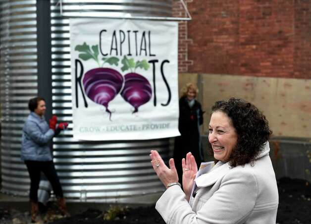 Capital District Community Garden executive director, Amy Klein celebrates the unveiling of the new name for the Capital District Community Gardens during the grand opening of the Urban Grow Center Wednesday morning, Dec. 3, 2014, in Troy, N.Y. (Skip Dickstein/Times Union) Photo: SKIP DICKSTEIN / 00029638A