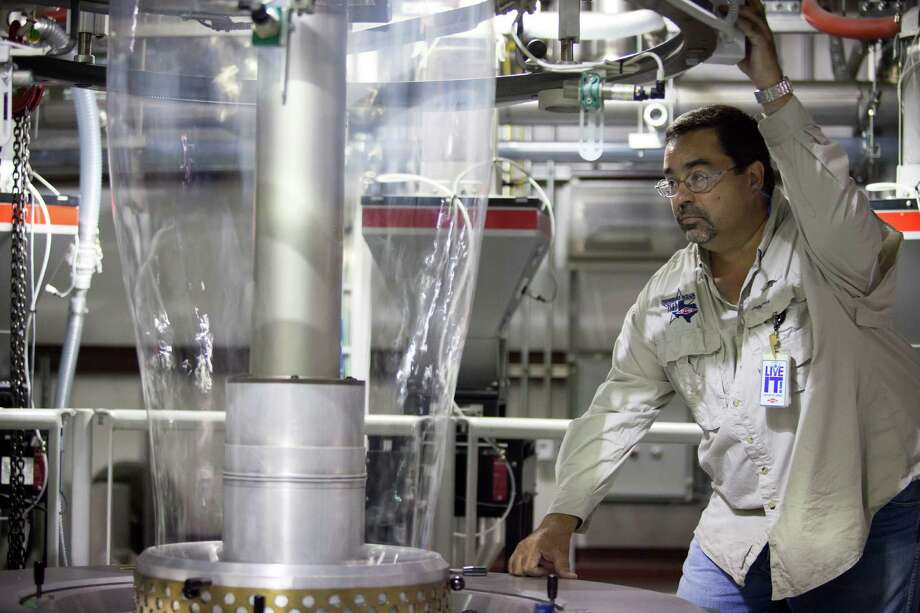 John Presa, a senior researcher for Dow Chemical, inspects film being blown from an extruder at a Dow research and development facility in Freeport. The petrochemical industry, which has been investing billions to expand and build new plants to take advantage of cheap domestic gas, remains optimistic that falling prices won't thwart the epic comeback underway. Photo: MICHAEL STRAVATO, STR / New York Times / NYTNS