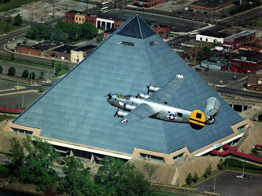 A vintage World War II B-24 Liberator bomber flies over the Pyramid in Memphis, Tenn., in 2000. The 32-story glass-and-steel building, empty since 2007, will become a hunting and fishing store.  Photo: JACK GRUBER, MBR / THE COMMERCIAL APPEAL