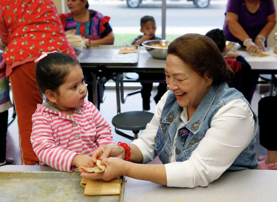 Angelise Altamirano, 2, learns how to make tamales from Virginia Casas. Casas said she loves working with children and liked seeing their expressions. Photo: Cynthia Esparza / Cynthia Esparza / For The San Antonio Express-News / ©2014 San Antonio Express-News
