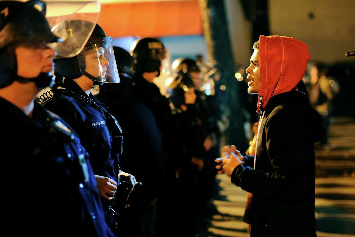 Tyreece Sherrill tries to talk with police that are blocking marchers path down Broadway during a demonstration in Oakland, CA, on Wednesday, December 3, 2014, protesting a grand jury decision not to indict an NYPD police officer that killed Eric Garner, a black man, by putting him into a chokehold during an arrest in July.