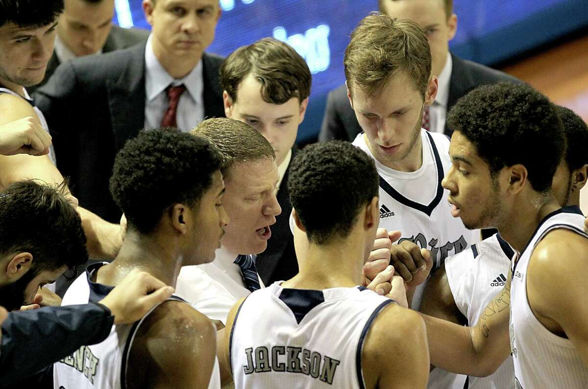 Rice Owls head coach Mike Rhoades huddles with his team against the Houston Baptist Huskies during a timeout in the first half on Wednesday, December 3, 2014 at the Tudor Fieldhouse at Rice University in Houston, TX. HBU was winning 32 to 25 at halftime.