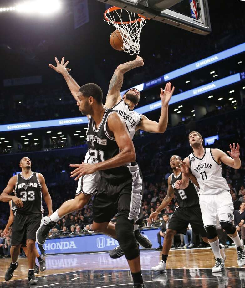 San Antonio Spurs forward Tim Duncan (21) collides with Brooklyn Nets guard Deron Williams as Williams goes up for a layup in the first half of an NBA basketball game at the Barclays Center, Wednesday, Dec. 3, 2014, in New York. Spurs forward Boris Diaw (33) and Nets center Brook Lopez (11) watch from the floor. (AP Photo/Kathy Willens) Photo: AP