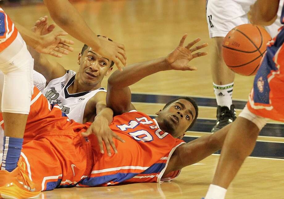 HBU guard Trey Patterson (10) won this loose ball from Rice guard Marcus Jackson as the Huskies beat their crosstown rival for the second year in a row. Photo: Thomas B. Shea, Freelance / © 2014 Thomas B. Shea