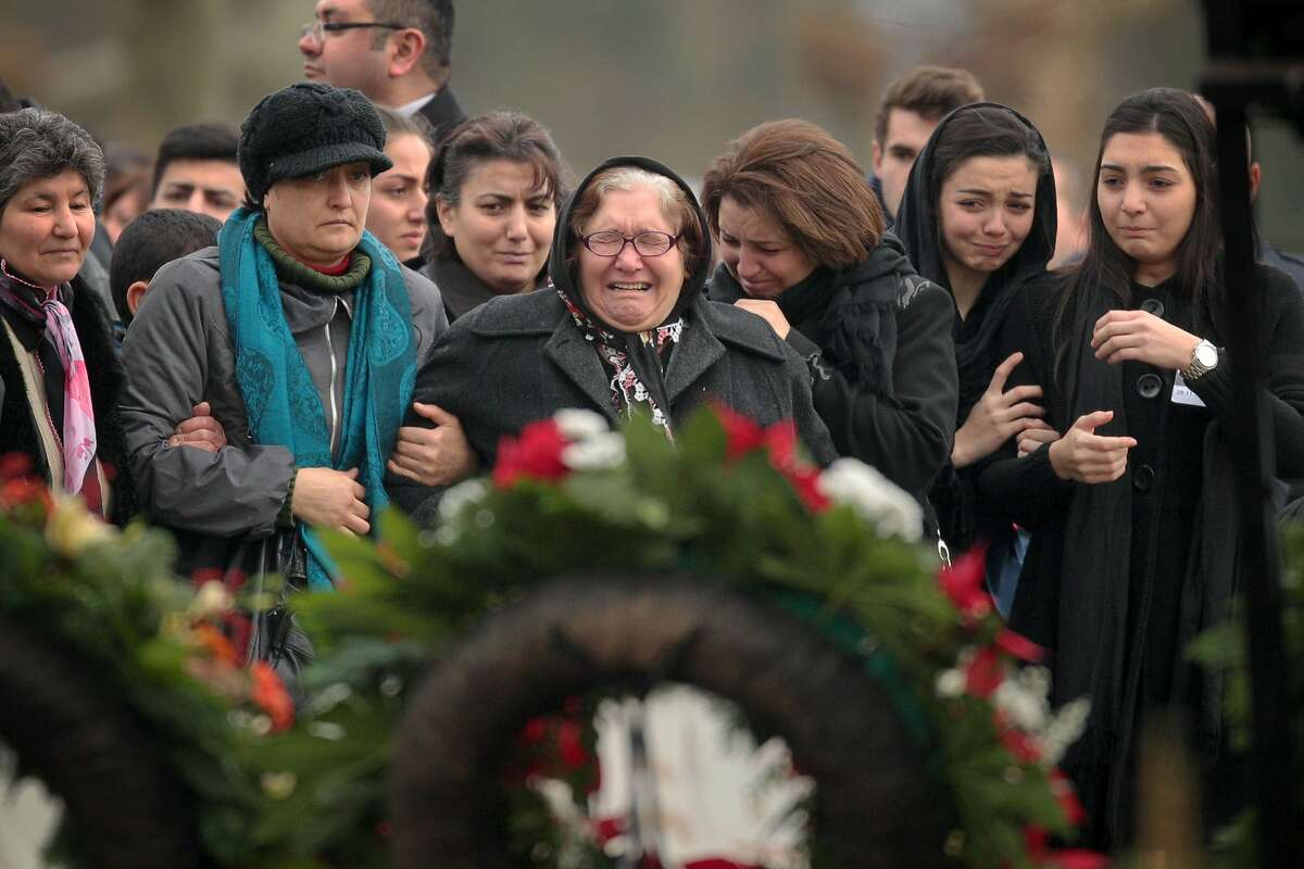 TOPSHOTS Mourners cry as they stand in front of the grave of Tugce Albayrak during her burial on December 3, 2014 at the cemetery in Bad Soden-Salmünster, western Germany. Hundreds of mourners attended the burial in Bad Soden-Salmünster and the funeral service in Waechtersbach for the young woman of Turkish origin who was attacked and later died after confronting a male group harrassing two teenage girls, sparking public outrage. AFP PHOTO / DPA / FREDRIK VON ERICHSEN / GERMANY OUTFREDRIK VON ERICHSEN/AFP/Getty Images
