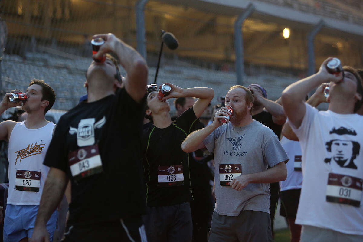 Runners chug their first beer before running their first lap during the Beer Mile Open - Heat 1 race at the Flotrack Beer Mile World Championships at the Circuit of the Americas in Austin on Wednesday, Dec. 3, 2014.
