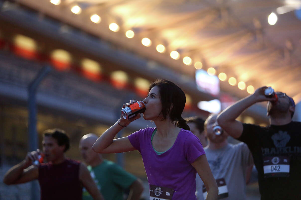 Marilyn Brown of Austin chugs a beer as she competes in the Race Heat 1 race during the Flotrack Beer Mile World Championships at the Circuit of the Americas in Austin on Wednesday, Dec. 3, 2014.